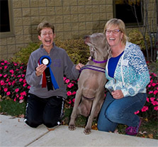 Dog Trainer Margaret Simek with happy client and their dog.
